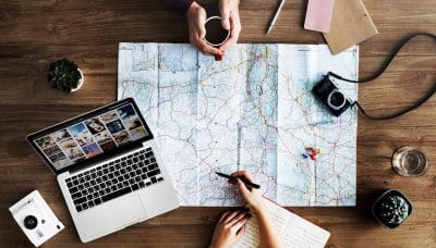 couple planning a trip with a map and computer