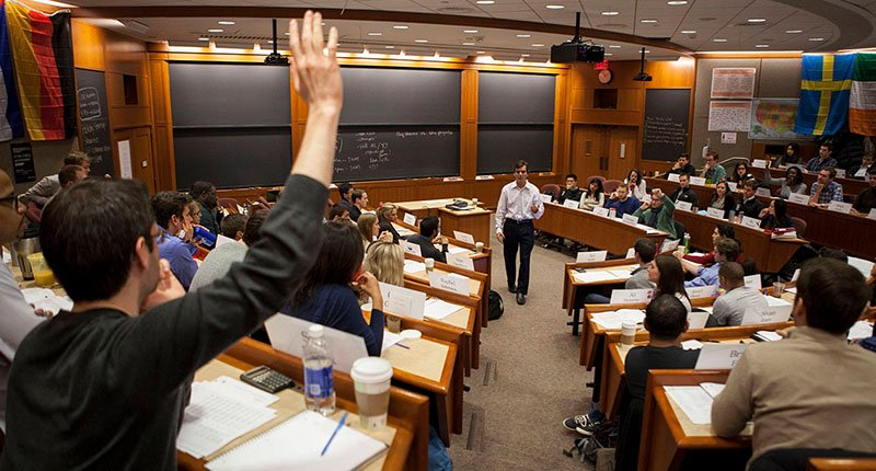 student raising hand in college lecture hall